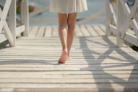 bare foot or legs of slim woman walks on wooden bridge pier to the seaside, feel freedom and comfortable walking alone close to beach nature Stock fotó