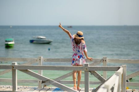 young woman standing on wooden bridge, cheer up hand the air with hat, enjoy the sea beach in summer vacation and long holidays, tourist in island travel Stock fotó