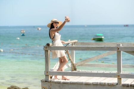 tourist enjoy selfie the view of the sea on wooden bridge, travelling on island of tourist place at seaside Imagens