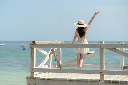young woman standing on wooden bridge, cheer up hand the air with hat, enjoy the sea beach in summer vacation and long holidays, tourist in island travel Imagens