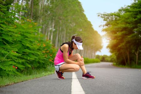 Sport runner woman getting hurt on legs alone on the lane of road park
