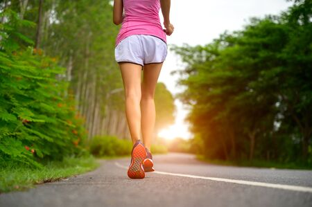 legs of healthy woman jogging alone at daily morning in public park, daily exercise workout running of woman