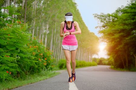 woman runner set the running watch to concentrate rate of heart timing for review health