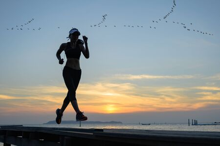 silhouette of woman jogging alone at daily run on the wooden jetty bridge or pier, daily exercise workout running at light of sunset Stock fotó