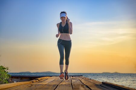 healthy slim woman jogging alone at daily morning on the wooden jetty bridge or pier, daily exercise workout running at light of sunset, trail competition at sea Stock fotó