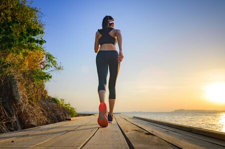legs of healthy woman jogging alone at daily morning on the wooden jetty bridge or pier, daily exercise workout running at light of sunset, trail competition at the sea