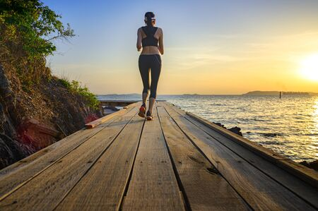 healthy woman jogging alone at daily morning on the wooden jetty bridge or pier, daily exercise workout running at light of sunset, trail competition at the sea