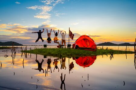 tourist camping stay jumping cheerfully on the small island in the lake at lowest tide of summer, camping preparation for stay over night at sunset scenery Stock fotó