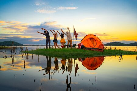 tourist camping stay hand up in the air, cheerfully on the small island in the lake at lowest tide of summer, camping preparation for stay over night at sunset scenery