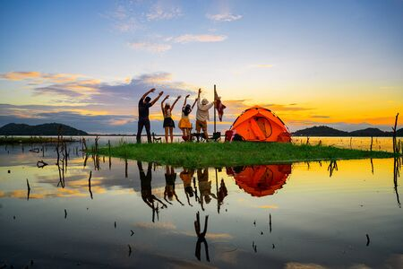tourist camping stay cheerfully on the small island in the lake at lowest tide of summer, camping preparation for stay over night at sunset scenery Stock fotó