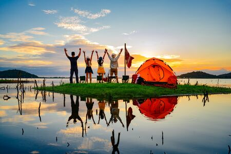 tourist camping enjoy hand up in the air, cheerfully on the small island in the lake at lowest tide of summer, camping preparation for stay over night at sunset scenery