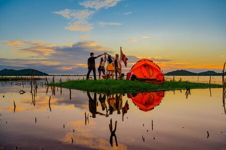 tourist camping enjoy hand up touching together in the air, cheerfully on the small island in the lake at lowest tide of summer, camping preparation for stay over night at sunset scenery