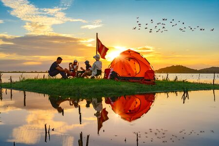 tourist camping enjoy camping on the small island in the lake at lowest tide of summer, camping preparation for stay over night at sunset scenery Stock fotó