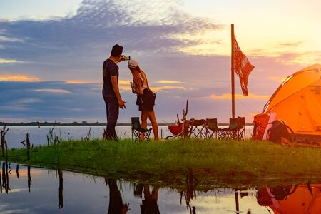 couple lover tourist camping enjoy selfie by mobile phone, cheerfully on the small island in the lake at lowest tide of summer, camping preparation for stay over night at sunset scenery