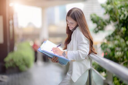 working woman in busy of involve business on street of city town, working online anytime and anywhere to reach customer satisfy