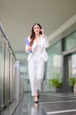freelance business working woman in keep talking of business on phone, working outdoor online anytime and anywhere to reach customer satisfy