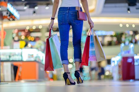 achterkant van slanke gelukkige vrouw en vrolijk in winkelcentrum, kopen en winkelen consumentisme met veel tassen in beide handen
