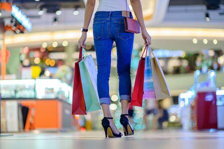 Rückseite einer schlanken, glücklichen Frau und fröhlich im Einkaufszentrum, Kauf- und Einkaufskonsum mit vielen Taschen, die in beiden Händen gehalten werden