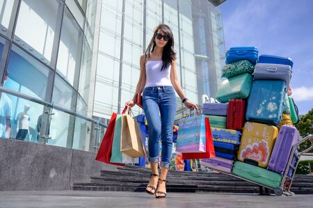 slender happy woman and joyful in shopping mall center, buying and shopping consumerism with many bags holding in both hands