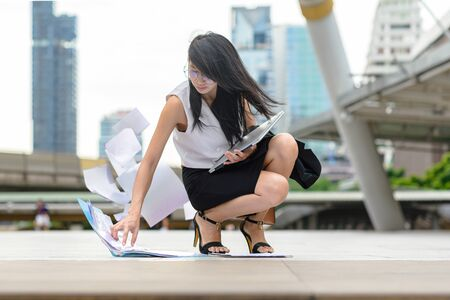 working office woman in busy motion at rush hours by drop documents paper to the floor in public place, sitting to collect dropped paper in working rush hours
