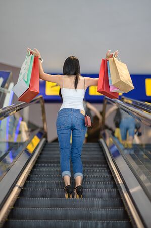 back of slender happy woman and joyful in shopping mall center, buying and shopping consumerism with many bags holding in both hands, walks on escalator lift stair up
