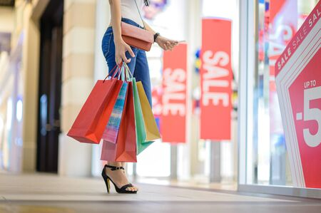 slender happy woman holding shopping in hand at shopping mall center, willing credit card to buying and shopping consumerism with many bags already are holding in hand Stock Photo