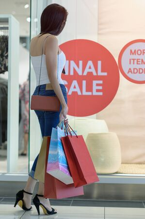 Shopping bags in hand of slender woman, looking in decision to shopping more in discount mall center, buying and shopping consumerism