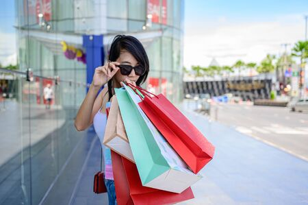 shopping bags in hand of slender woman joyful in shopping mall center, buying and shopping consumerism with many bags holding are in hand