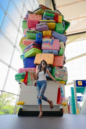 woman enjoy shopping on the mall center, cheerfully at shopping mall, hand up to the air at most happy enjoyment, Luggages and trolley Model in along happiness