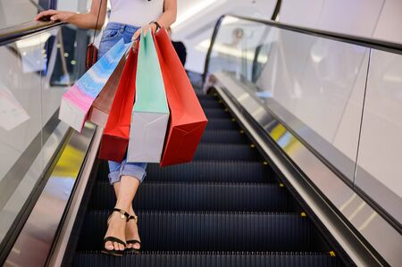 shopping bags in hand of happy woman enjoy walks upon escalator in shopping mall center, buying and shopping consumerism with many bags holding are in hands