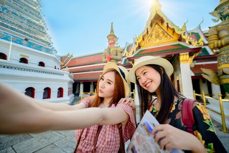 young tourist women enjoy taking selfie picture in the palace temple in Bangkok of Thailand, Emerald Buddha Temple, Wat Phra Kaew, Bangkok Royal Palace popular tourist place