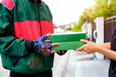 pizza boxes case being delivery to the customer services from door to door at swift services, hand of pizza man and house keeper holding pizza boxes odering