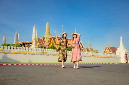 young tourist women walking in walk pathway of the palace temple in Bangkok of Thailand, Emerald Buddha Temple, Wat Phra Kaew, Bangkok Royal Palace popular tourist place
