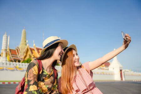 young tourist women enjoy traveling in sitting selfie picture in front of the palace temple in Bangkok of Thailand, Emerald Buddha Temple, Wat Phra Kaew, Bangkok Royal Palace popular tourist place
