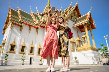 young tourist women in taking selfie picture, enjoy travel in the palace temple in Bangkok of Thailand, Emerald Buddha Temple, Wat Phra Kaew, Bangkok Royal Palace popular tourist place