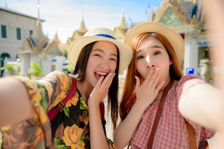 tourist women in exciting take selfie picture, enjoy travel in the palace temple in Bangkok of Thailand, Emerald Buddha Temple, Wat Phra Kaew, Bangkok Royal Palace popular tourist place