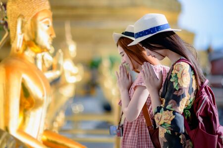 young woman tourist praying pay respect to Buddha statue in the palace temple in Bangkok of Thailand, Emerald Buddha Temple, Wat Phra Kaew, Bangkok Royal Palace popular tourist place