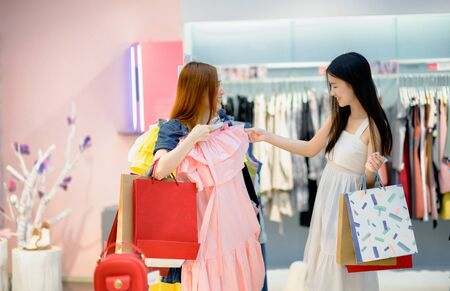 women enjoy shopping outdoor cheerfully at shopping mall, fitting to try dressing new brand, buying and shopping consumerism with many bags holding in hands