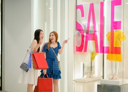 happy women and joyful in shopping mall center, buying and shopping consumerism with many bags holding in both hands Stock Photo