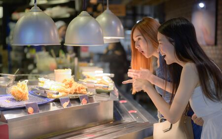 women exciting to having meals in food court of the shopping mall Stock Photo