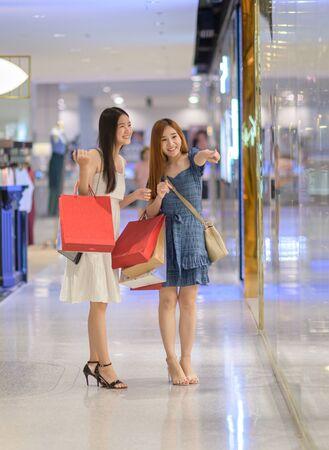 jeunes femmes heureuses à la recherche de biens personnels articles avec joyeux dans le centre commercial, achat et shopping consumérisme avec de nombreux sacs tenant dans les deux mains Banque d'images