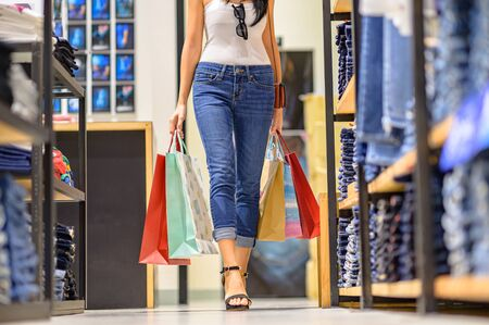 slender happy women and joyful and exciting in shopping mall center, buying and shopping consumerism with many bags holding in both hands