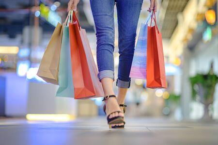 Die Beine der Frau genießen das Einkaufen im Einkaufszentrum, die Hand, die das Einkaufen hält, den Konsum kauft und einkauft, das Einkaufen im Sommer-Discounter genießt