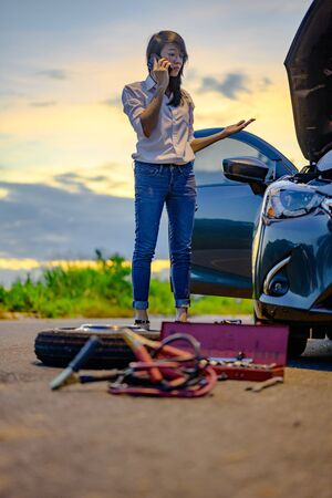Woman try to fix problem of car by herself with belonging tools, need help and assistant at dark of the night, scary and worry alone in the dark, car engine failure or tire need replacement