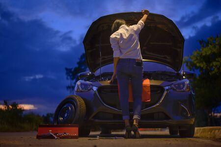 Frauen versuchen, das Problem des Autos mit den dazugehörigen Werkzeugen selbst zu beheben, brauchen Hilfe und Assistenten in der Dunkelheit der Nacht, beängstigend und sorgen sich allein im Dunkeln, Automotorausfall oder Reifen müssen ausgetauscht werden