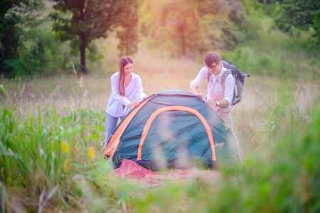 Couple lover help on each other prepare tent to stay over night in middle of wildflowers field
