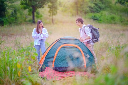 woman is in praise and most cheerfully motion to the man on success prespare tent to stay over night
