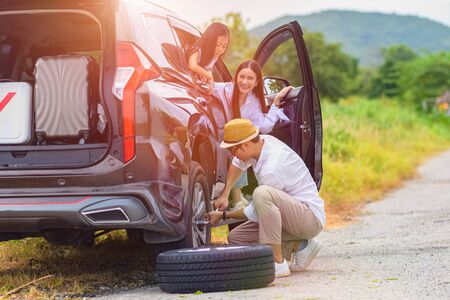 happy family in car tire flat during traveling, finish tire replacement by leader father, cheerfully at the end 写真素材