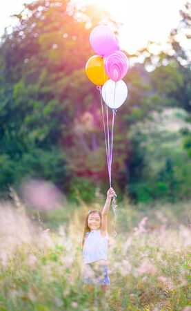 Girl children enjoy playing around in wildflower meadow with multicolors balloons holding in hands 写真素材