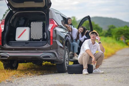 happy family in car tire flat during traveling, calls for help 写真素材